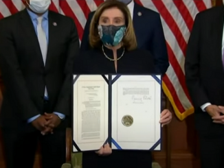 Nancy Pelosi holds the signed impeachment article